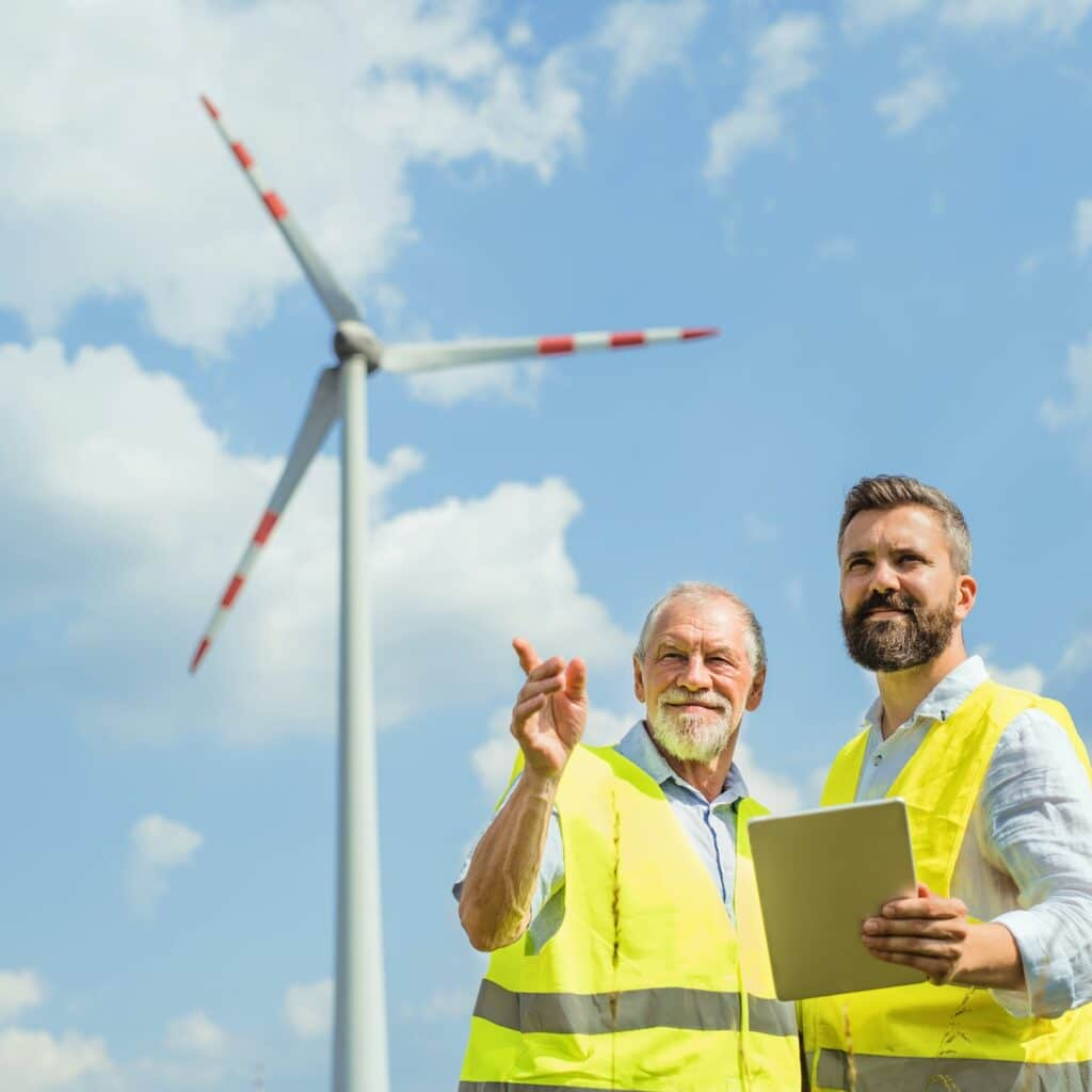 Engineers standing on wind farm, making notes